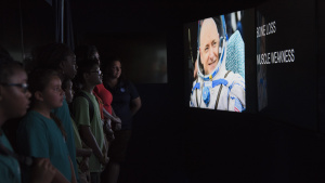 Participants watch a video in a mobile exhibit