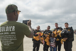 "U.S. Army Parachute Team ""Golden Knights"" members pose with an air show attendee during the 2017 Joint Base Andrews Air Show"