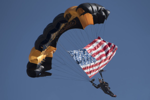 A member of the Army Golden Knights parachute team descends upon the crowd with the American flag at the 2017 Andrews Air Show